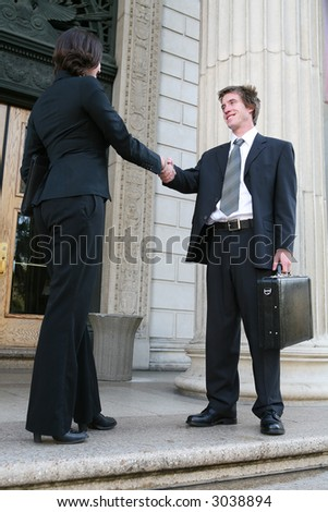 Two lawyers shaking hands outside the court building