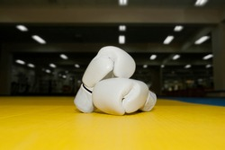 two leather white Boxing gloves for Kudo wrestling on a yellow tatami on the background of the gym