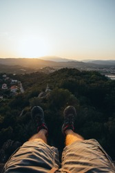 Two legs hanging on the heights overlooking a beautiful sunset in Palafolls, Spain
