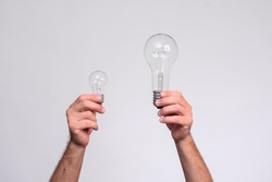 two light bulbs in men's hands. large and small incandescent lamps. on a white background.