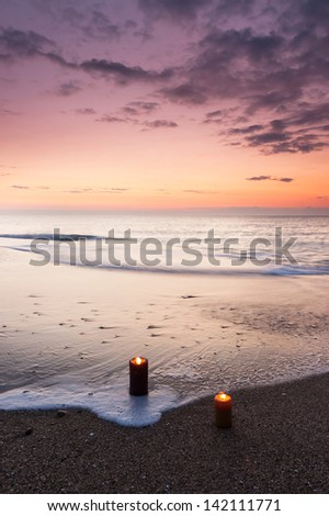 Two lighted candles on the beach at sunrise #142111771