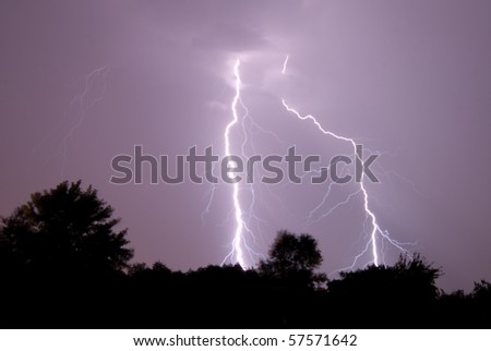 Two lightning strikes full of branching hit the earth at the same time.