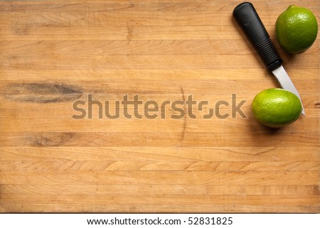 Two limes waiting to be cut on a worn butcher block cutting board - stock photo