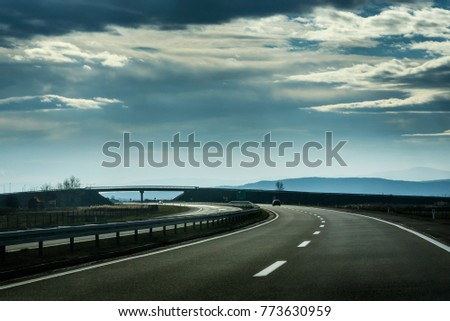 Two line wide highway on a cloudy winter day leading to the mountains through rural landscape #773630959