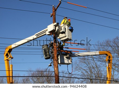 Two lineman working to restore power on electrical lines.
