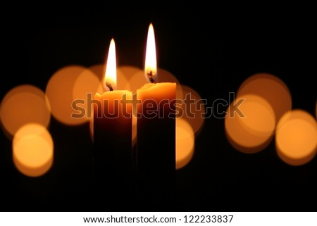 Two lit candles with lit candles in the background