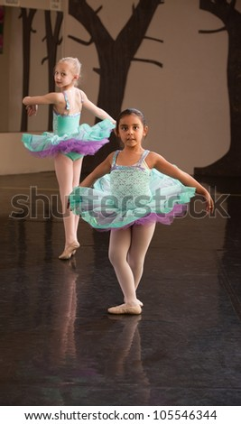 Two little ballet students practice in a dance studio