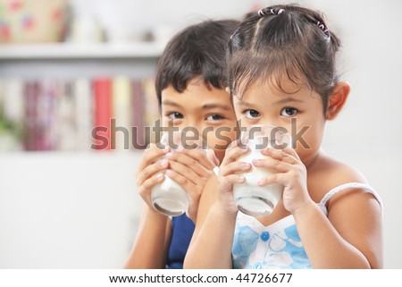 Two little boy and girl drinking milk at home