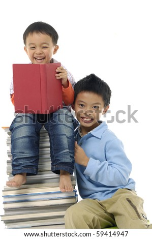 Two little boy sitting on pile of books having fun together