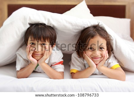 Two little boy smiling relaxing in the bedroom