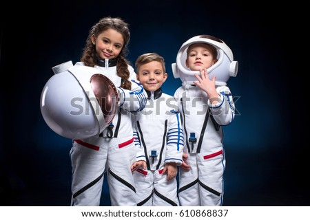 Two little boys and girl in space suits playing astronauts looking at camera