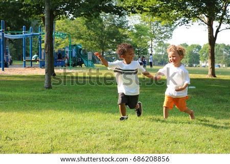 Two little boys are holding hands and running through the park.  #686208856