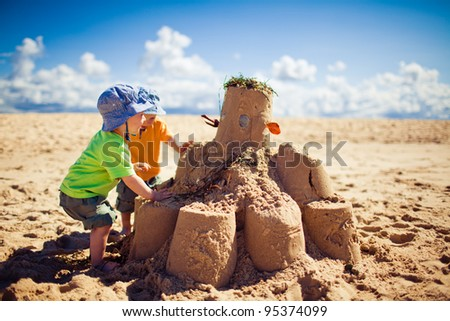 Two little boys building large sandcastle on the beach