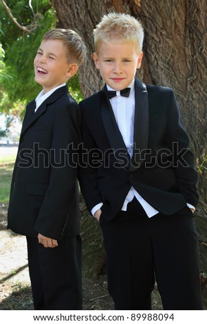 two little boys dressed in tuxedo standing near tree at sunny day outdoor; focus on boy on right