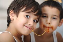 Two little boys eating spaghetti
