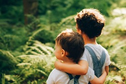 Two little boys, friends hug each other in summer sunny day in the forest. Brother love. Back view. Looking forward in the future.