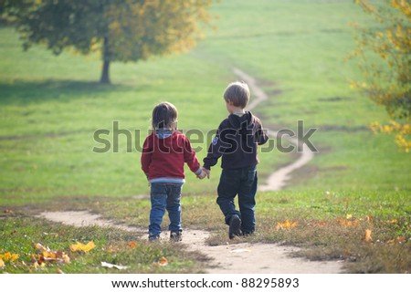 Two little boys holding hands following the path