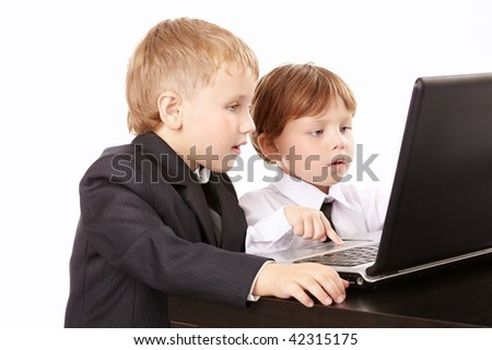 Two little boys in business suits together look in the screen of the laptop, isolated