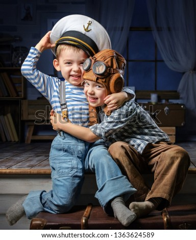 Two little boys in suits of the captain of the ship and the pilot play in the evening in the room #1363624589