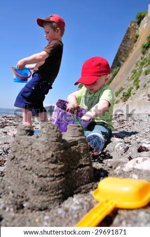 two little boys, making sandcastles on the beach.