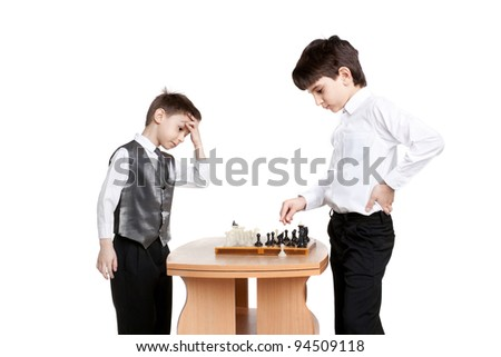 two little boys playing chess in studio