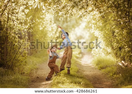 Two little boys playing in the garden and collect a bouquet of bird cherry