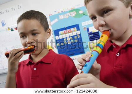 Two little boys playing musical instrument in class