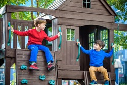 Two little boys playing together and having fun. Lifestyle family moment of siblings on playground. Kids friends play on tree house climbing on rope or stairs.