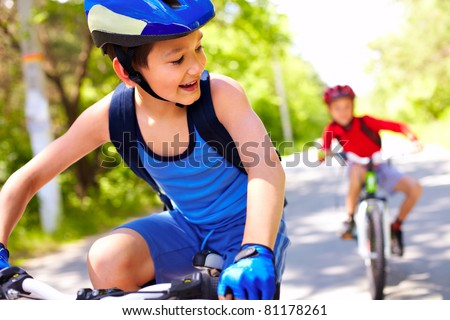 Two little boys riding bikes one after another