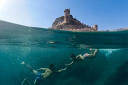 Two little boys snorkeling with a castle in the background