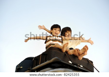 Two little boys traveling on bags, the top of the car