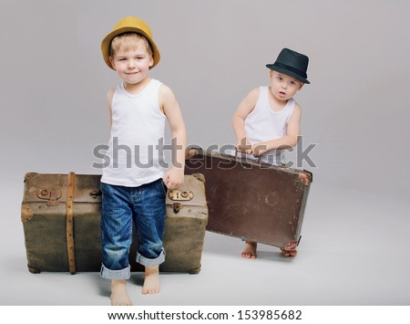Two little boys walking with suitcases