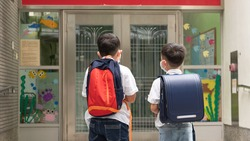 Two little boys with backpack are walking into the school. School kids are in front of the gate.Healthy adorable children, brothers/best friends/siblings are waiting to get in the class.