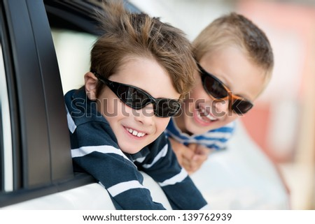 Two little boys with shades playing inside the car