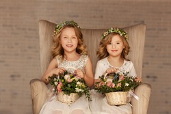 two little bridesmaid sitting in a chair with bouquets