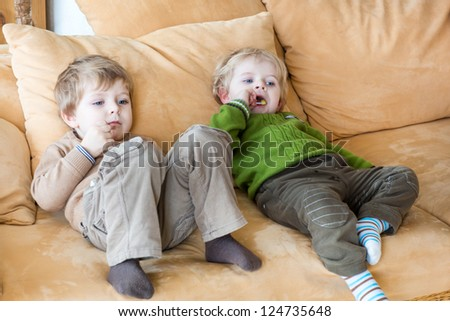 Two little brother boys watching tv and eating candy indoor