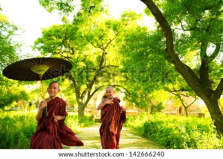 Two little Buddhist monks running outdoors under shade of green tree outside monastery Myanmar