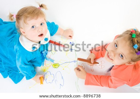 Two little caucasian girl painting and look up