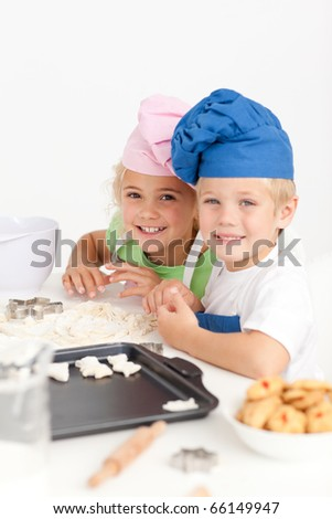 Two little chefs preparing cookies in the kitchen and smiling at the camera