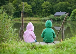 Two little child sitting together and looking at the lake view
