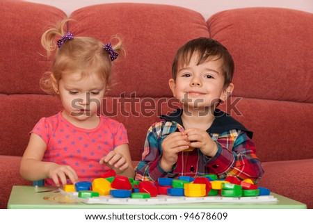 Two little children are playing at the table - stock photo