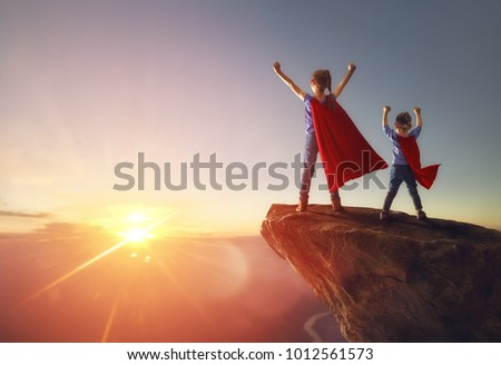 Two little children are playing superhero. Kids on the background of sunset sky. Girl power concept #1012561573