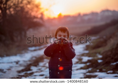 Two little children, boys, exploring nature with binoculars, looking at sunset