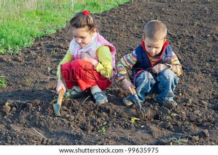 Two little children planting seeds and weed beds in the garden