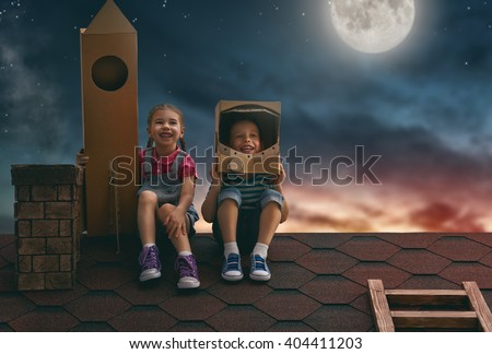 Two little children playing astronauts. Child boy in an astronaut costume and child girl with toy rocket standing on the roof of the house and looking at the sky and dreaming of becoming a spacemen.