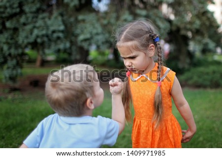 Two little children, sister and brother, quarreling and ready to beat each other crying during their walking, bad mood, negative emotion, upbringing and family concept, summer outdoor #1409971985