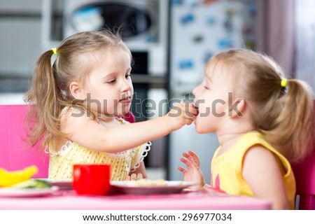 Two little children toddlers eating meal together, one girl feeding sister in sunny kitchen at home