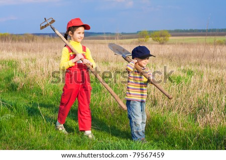 Two little children walking on field with garden tools