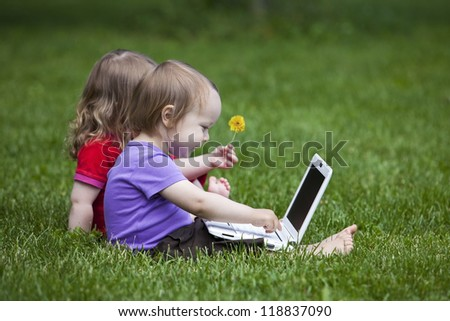 Two little children working together on the meadow with a laptop.