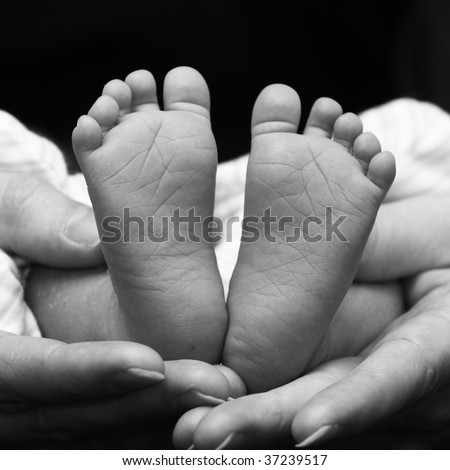 two little feet in the shape of heart in cuddling hands